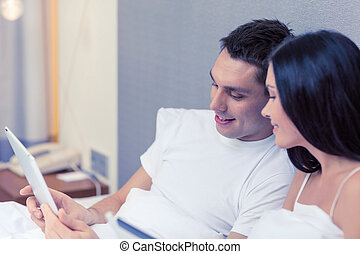 smiling couple in bed with tablet pc computers - hotel,...