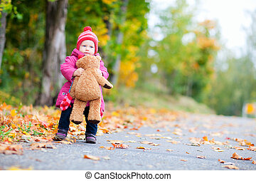 Toddler girl with teddy bear outdoors on autumn day -...
