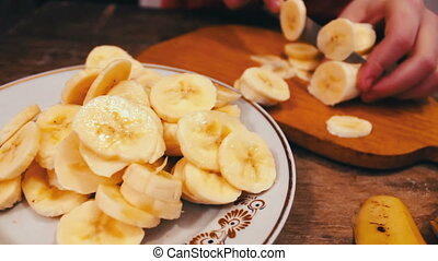 Close-up of cutting banana on wooden board with knife