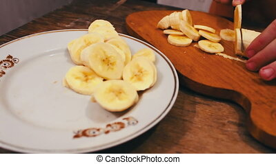 Close-up of cutting banana on wooden board with knife - The...