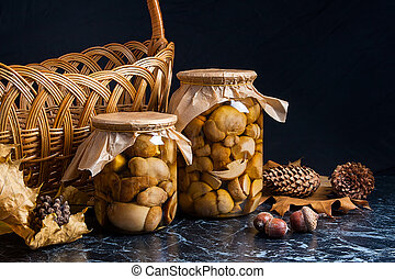 Two glass jars with wild marinated mushrooms on black marble background.