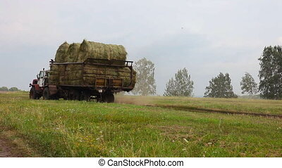 Big tractor. - Tractor exports rolled hay from the field....