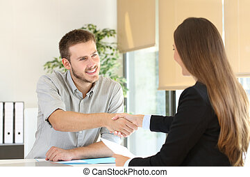 Employee and boss handshaking after a job interview - Happy...