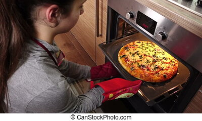 Girl pull out hot pizza from oven at kitchen interior