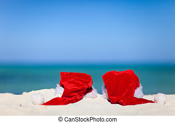 Two red Santa hats on beach - Two red Santa hats on exotic...