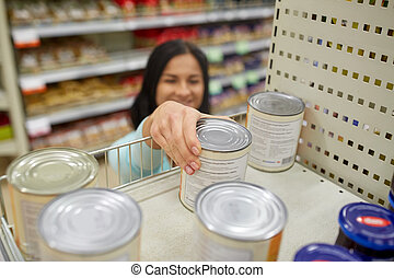 woman taking can with food from shelf at grocery - shopping,...