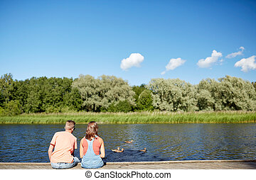 couple on river berth looking at swimming ducks - summer,...