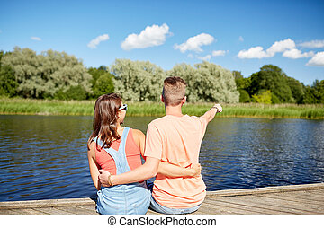 happy couple pointing finger on summer river berth -...