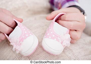pink booties for newborn baby in hands of dad. pregnancy -...
