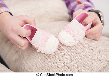 pink booties for newborn baby in hands of dad. pregnancy