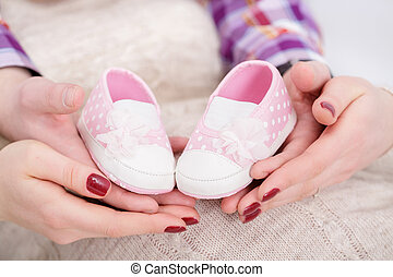 pink booties for newborn baby in hands of mum and dad....