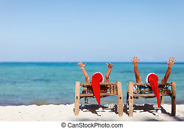 Couple in Santa hats on tropical beach - Happy romantic...