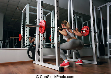 Young sexy blonde european girl in the gym doing squat with barbell in front of the mirror