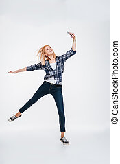 Happy young lady holding phone while jumping. - Image of...