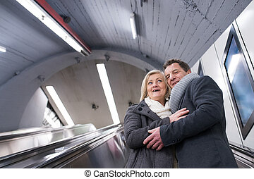 Senior couple standing at the escalator in Vienna subway