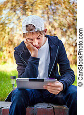Sad Teenager with Tablet Computer sit outdoor