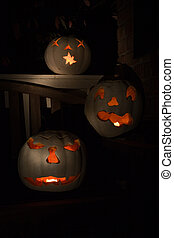 Three lit white jack o-lanterns - Three lit white jack...
