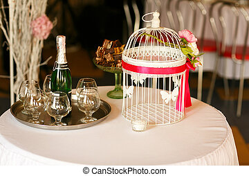Wedding table decor. White bird cage with red ribbon over it