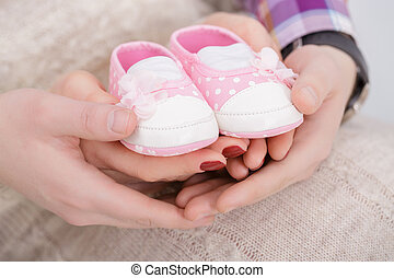 pink booties for newborn baby in hands of mum and dad. pregnancy