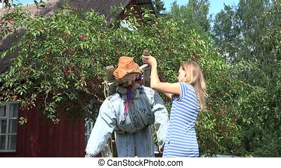 villager girl stand scarecrow on cherry tree to protect...