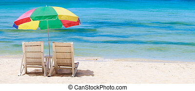 Panorama of tropical beach with chairs and umbrella -...