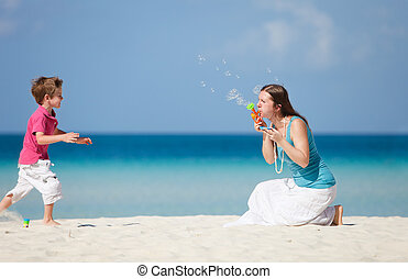 Mother and son making soap bubbles on tropical beach
