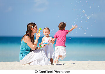 Family making soap bubbles - Young mother making soap...