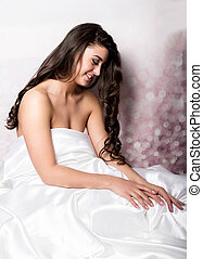 pretty female in peignoir sleeping on bed under silk sheets.