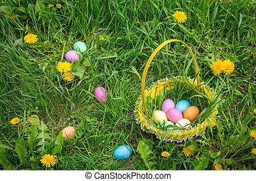 background with colorful easter eggs on lawn and in basket -...