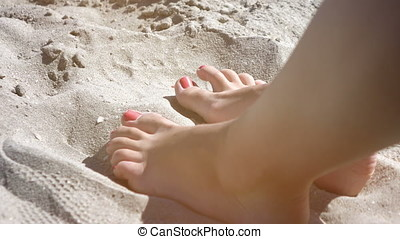 Feet in sand tapping a rhythm in real slow motion