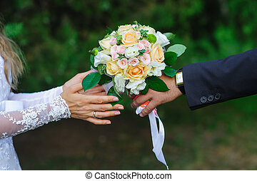 Groom gives bride a wedding bouquet in summer park