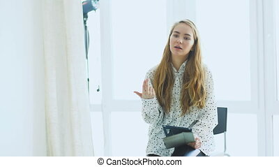 Young woman make-up artist talking in conference. Studio...