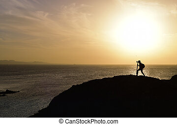 man taking a picture at dusk - the silhouette of an...