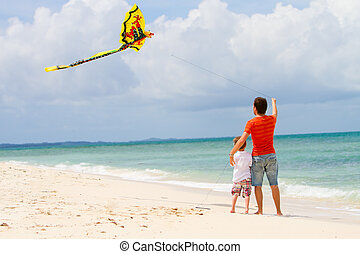 Father and son flying kite on beach