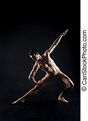 Muscular young athlete stretching in the black studio