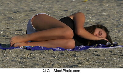 Young woman sleeping on the beach