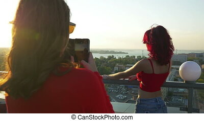 Two women having photo session with smartphone on a rooftop
