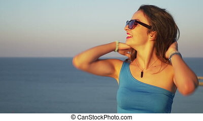 Beautiful young woman posing in photo session with the sea as a background on a rooftop