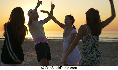 Four friends dancing on the beach at twilight