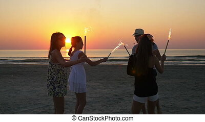 Group of friends dancing with fireworks on a sandy beach at sunrise