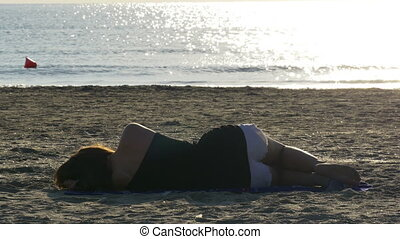 Young woman sleeping on a sandy beach