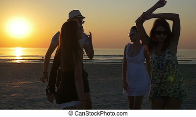 Young man dancing with three female friends on the shore of the ocean at twilight