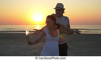 Couple dancing with a firework candle at the beach at sunrise