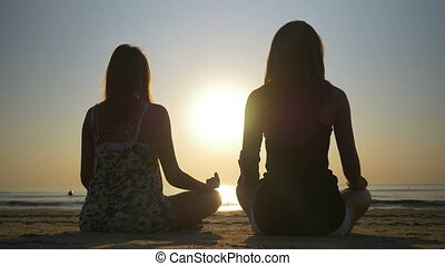 Two women meditating on the shore of the sea
