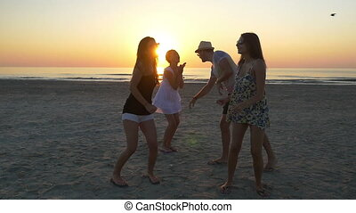 Group of young teenagers dancing on the beach at sunrise