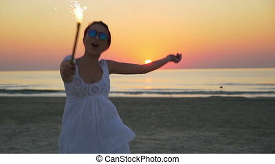 Young woman with a firework candle in her hand jumping happily at the beach