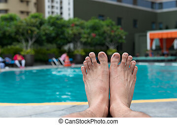 Man feet at swimming pool - View of bare man feet at...