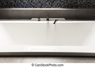 Bath with steely tap - White bath in modern bathroom with...