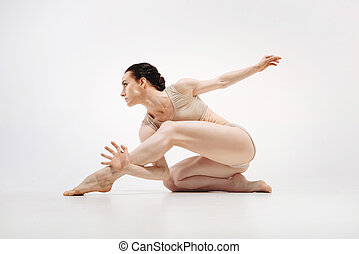 Muscular young athlete stretching in the white colored studio