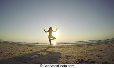 Young female making exercises on the beach